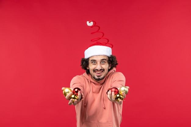Vue de face du jeune homme avec des jouets d'arbre de noël sur mur rouge