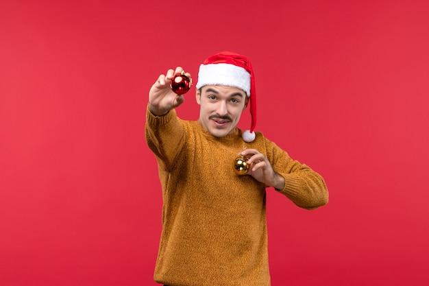 Vue de face du jeune homme avec des jouets en plastique sur le mur rouge
