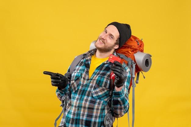 Vue de face du jeune homme joyeux avec backpacker tenant une carte de réduction