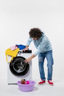 Vue de face du jeune homme avec lave-linge et vêtements sales sur mur blanc