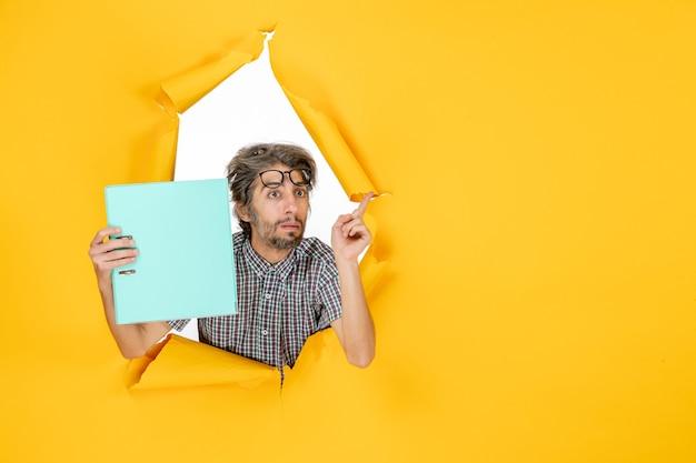 Vue de face du jeune homme lisant un fichier vert sur un mur jaune