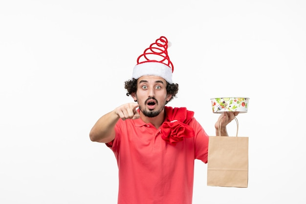 Vue de face du jeune homme avec livraison de nourriture sur mur blanc