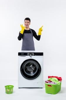 Vue de face du jeune homme avec machine à laver et vêtements sales sur mur blanc