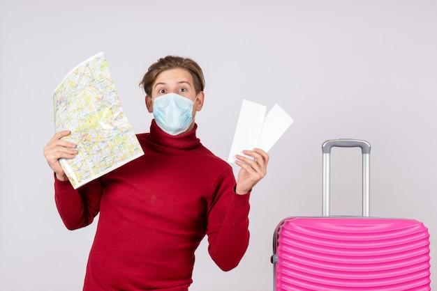 Vue de face du jeune homme en masque tenant des billets d'avion et une carte sur un mur blanc