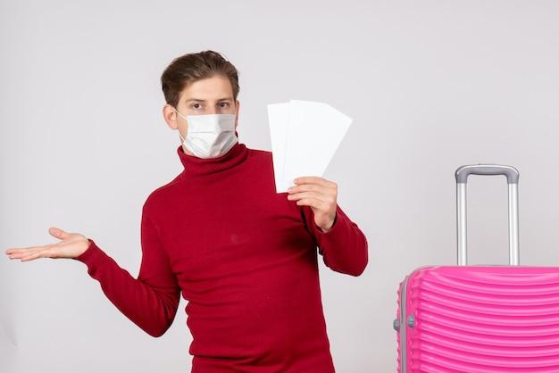 Vue de face du jeune homme en masque tenant des billets d'avion sur un mur blanc