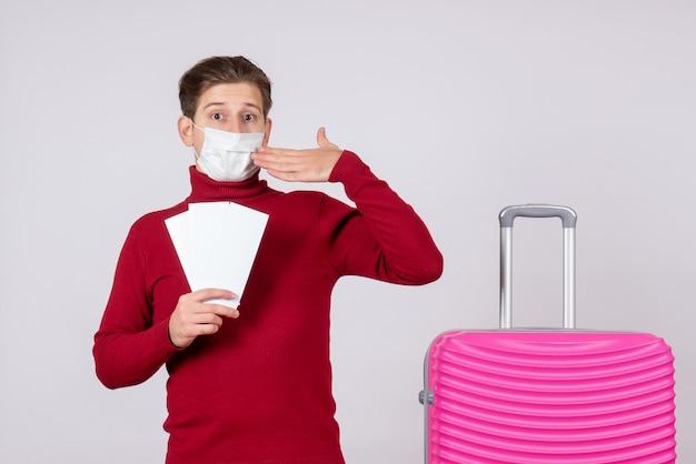 Vue de face du jeune homme en masque tenant des billets sur un mur blanc