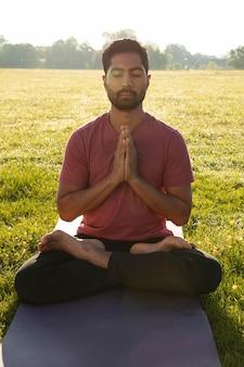 Vue de face du jeune homme méditant à l'extérieur sur un tapis de yoga