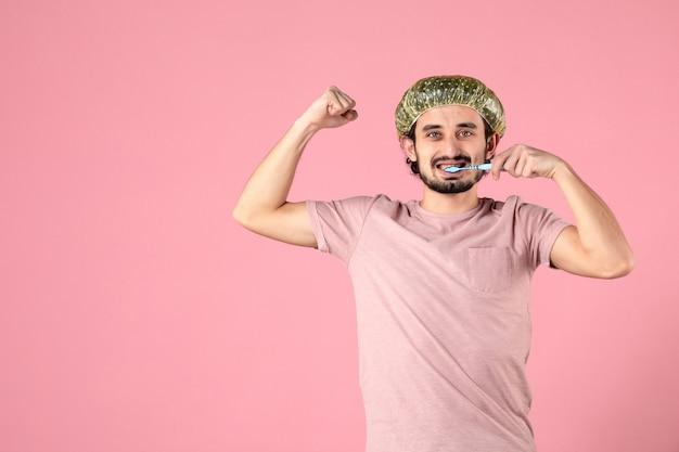 Vue de face du jeune homme nettoyant ses dents et fléchissant sur un mur rose clair