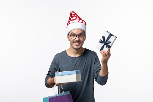 Vue de face du jeune homme avec des paquets et des cadeaux sur un mur blanc