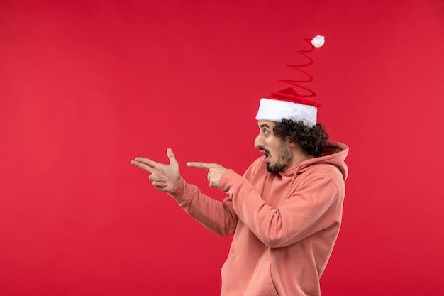 Vue de face du jeune homme avec pistolet tenant pose sur mur rouge