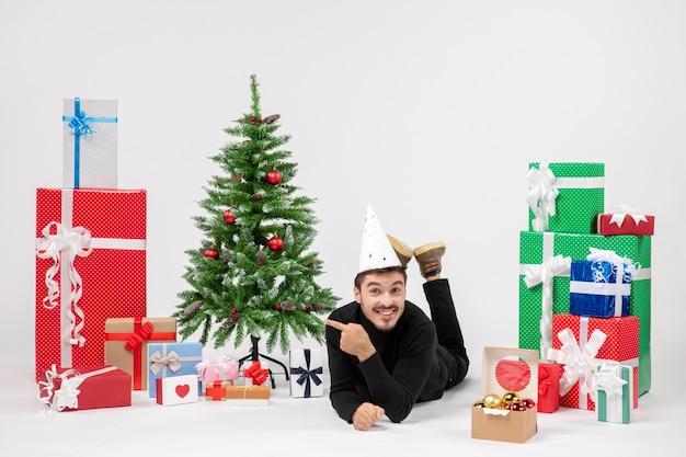 Vue de face du jeune homme portant autour des cadeaux de vacances sur le mur blanc