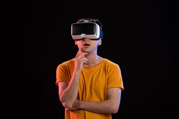 Vue de face du jeune homme portant un casque vr sur le mur sombre