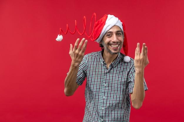 Vue de face du jeune homme portant un chapeau de jouet de noël sur le mur rouge