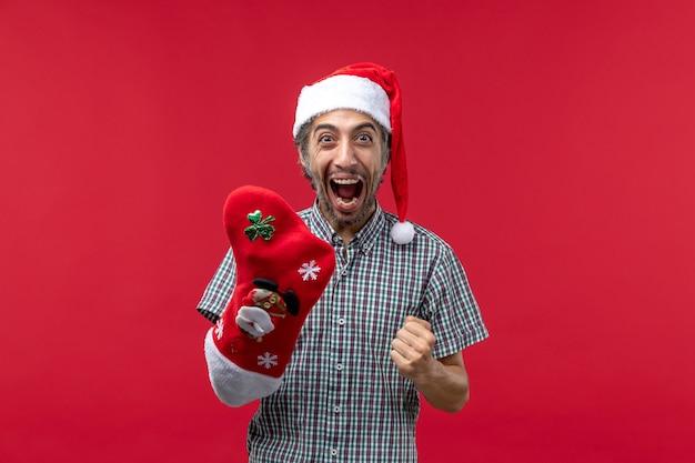 Vue de face du jeune homme portant des chaussettes de noël sur le mur rouge