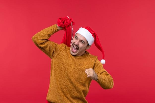 Vue de face du jeune homme portant un sac cadeau rouge sur mur rouge