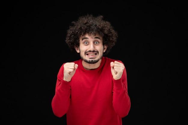 Vue de face du jeune homme en pull rouge sur le mur noir
