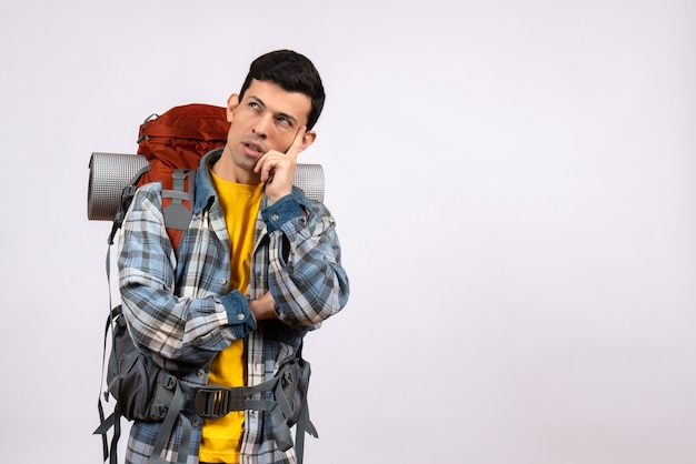Vue de face du jeune homme avec sac à dos mettant la main sur son menton pensant à quelque chose