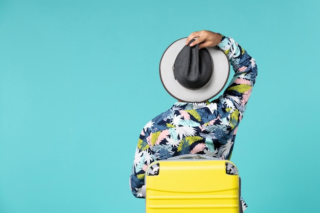 Vue de face du jeune homme avec un sac jaune portant un chapeau et la préparation pour le voyage sur le mur bleu