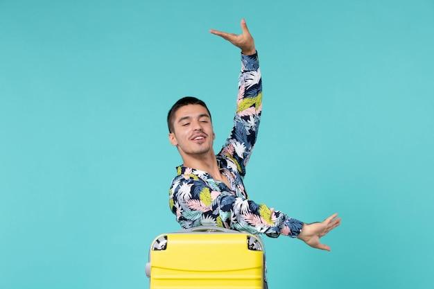Vue de face du jeune homme se préparant pour le voyage avec son sac jaune sur le mur bleu