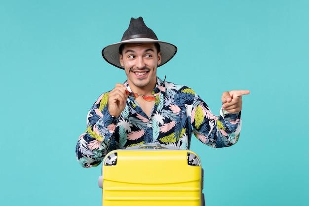 Vue de face du jeune homme avec son sac jaune se préparant pour le voyage en soulignant sur le mur bleu