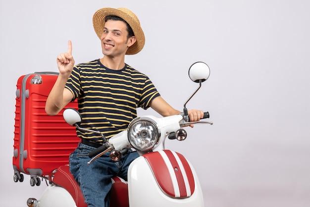 Vue de face du jeune homme souriant avec un chapeau de paille sur un cyclomoteur surprenant avec une idée