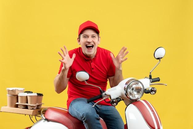Vue de face du jeune homme souriant émotionnel surpris portant un chemisier rouge et un chapeau livrant des commandes sur fond jaune