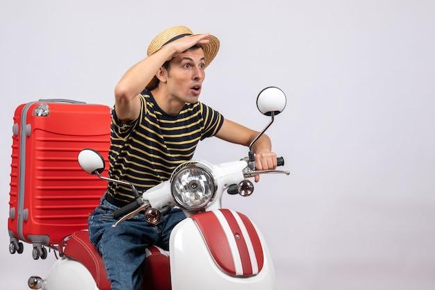 Vue de face du jeune homme surpris avec un chapeau de paille sur un cyclomoteur regardant quelque chose