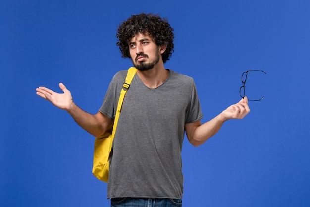 Vue de face du jeune homme en t-shirt gris portant un sac à dos jaune sur le mur bleu clair