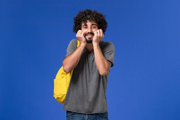 Vue de face du jeune homme en t-shirt gris portant un sac à dos jaune sur le mur bleu