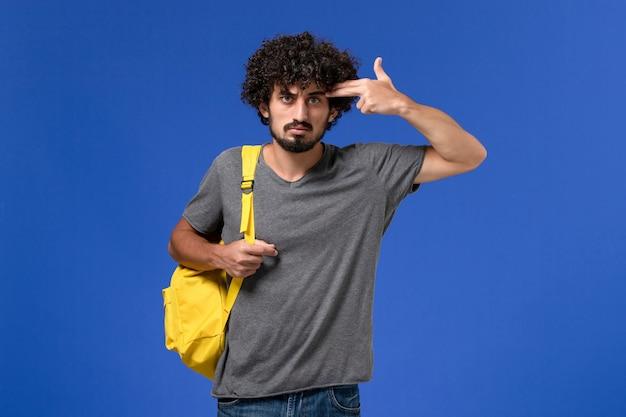 Vue de face du jeune homme en t-shirt gris portant un sac à dos jaune posant juste sur le mur bleu