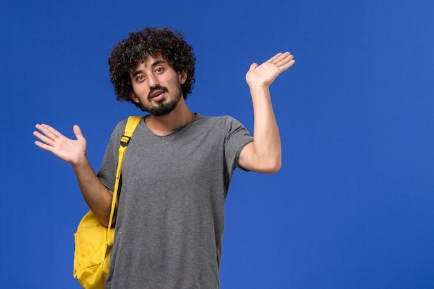 Vue de face du jeune homme en t-shirt gris portant un sac à dos jaune posant sur un mur bleu