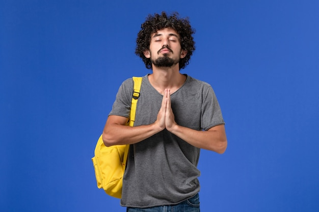 Vue de face du jeune homme en t-shirt gris portant un sac à dos jaune priant sur le mur bleu