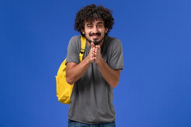 Vue de face du jeune homme en t-shirt gris portant un sac à dos jaune se réjouissant sur le mur bleu