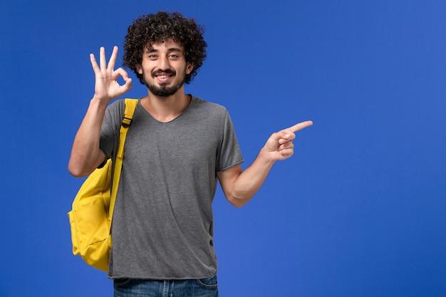 Vue de face du jeune homme en t-shirt gris portant un sac à dos jaune souriant sur le mur bleu