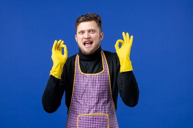 Vue de face du jeune homme en tablier faisant un signe okey debout sur un mur bleu