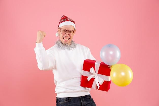 Vue de face du jeune homme tenant des ballons et présent se réjouir sur le mur rose