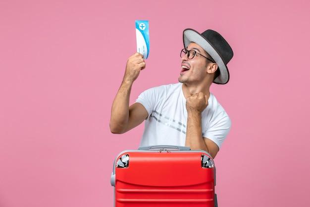 Vue de face du jeune homme tenant un billet d'avion pour des vacances sur le mur rose clair