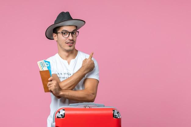 Vue de face du jeune homme tenant des billets d'avion et partant en vacances sur le mur rose