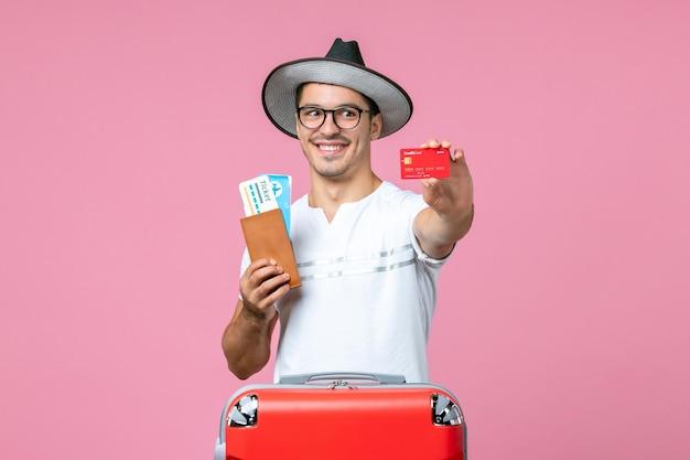Vue de face du jeune homme tenant des billets et une carte bancaire sur le mur rose