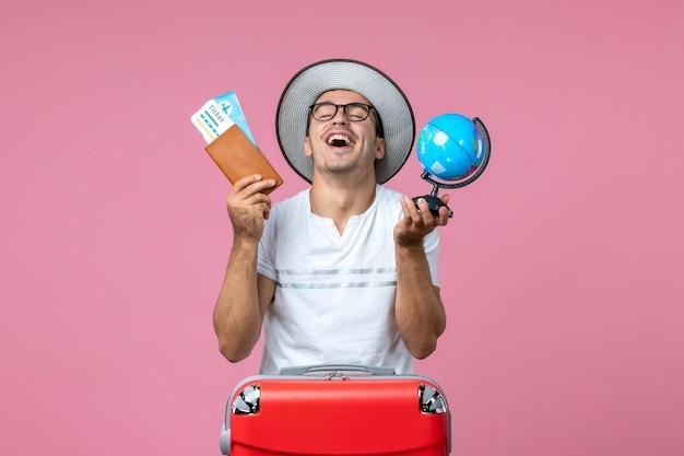 Vue de face du jeune homme tenant des billets et un petit globe sur un mur rose clair