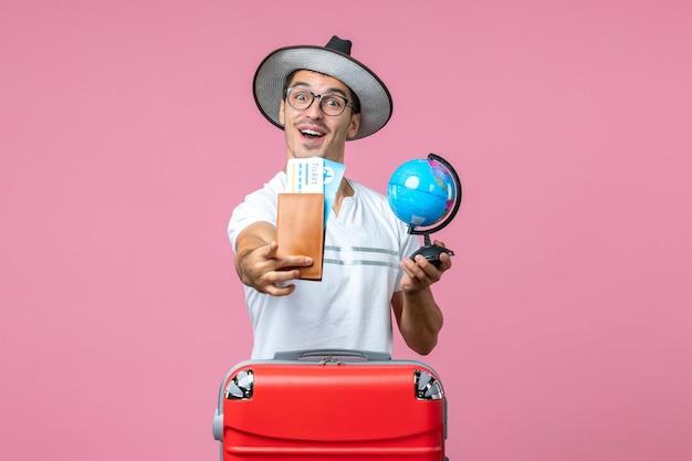 Vue de face du jeune homme tenant des billets et un petit globe sur le mur rose