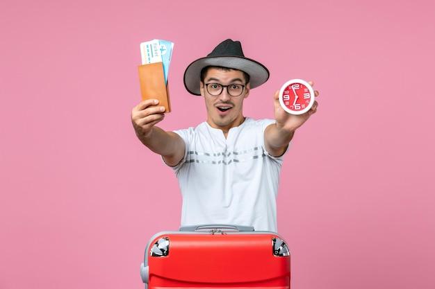 Vue de face du jeune homme tenant des billets de vacances et une horloge sur le mur rose