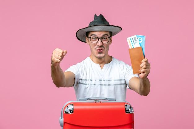 Vue de face du jeune homme tenant des billets de vacances sur le mur rose