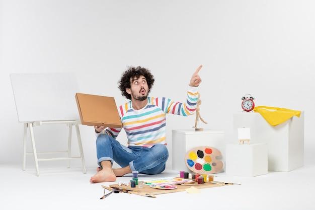 Vue de face du jeune homme tenant une boîte à pizza sur un mur blanc