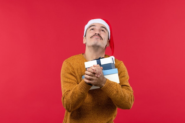 Vue de face du jeune homme tenant des boîtes présentes priant sur un mur rouge