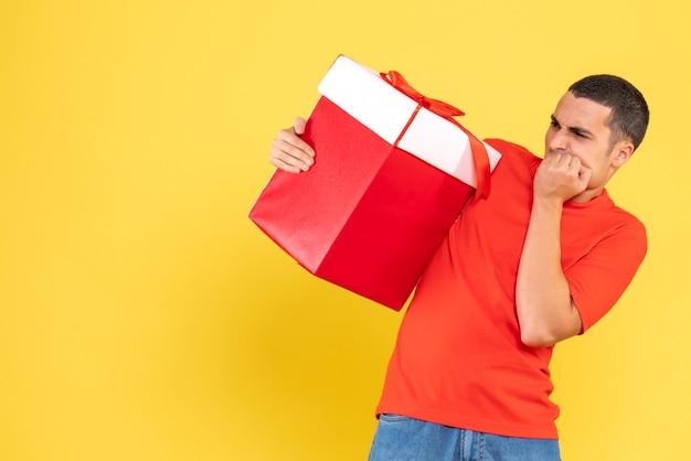 Vue de face du jeune homme tenant le cadeau de noël sur le mur jaune