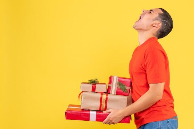 Vue de face du jeune homme tenant des cadeaux de noël sur mur jaune