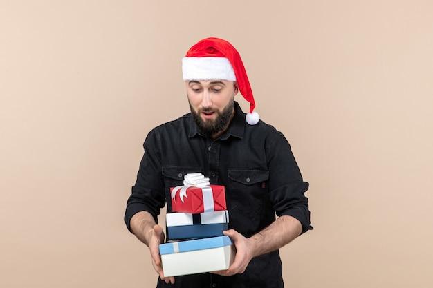 Vue de face du jeune homme tenant des cadeaux de vacances sur le mur rose