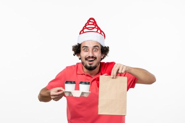Vue de face du jeune homme tenant un café de livraison sur un mur blanc