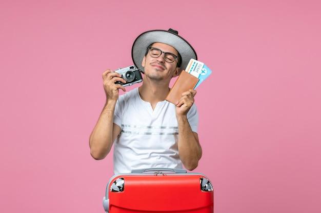 Vue de face du jeune homme tenant une caméra et des billets d'avion sur le mur rose